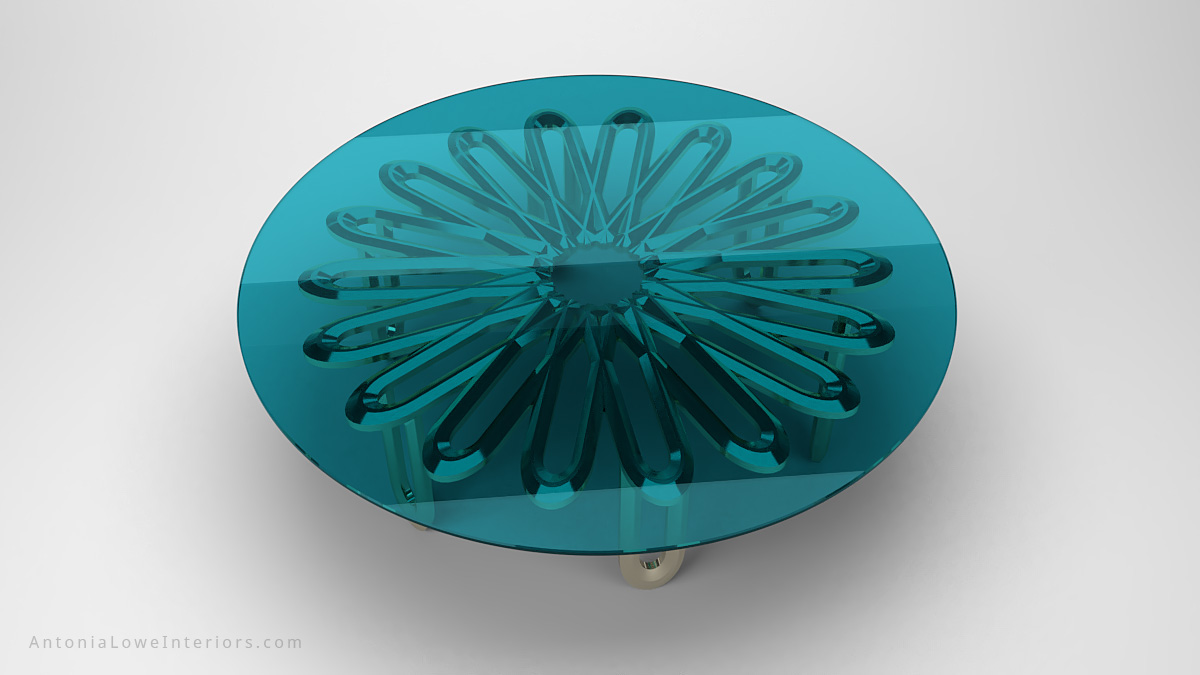 Top view Elegant Contemporary Floral Coffee Table clear teal glass round table top with metal floral detailing underneath supported by metal legs all in polished chrome