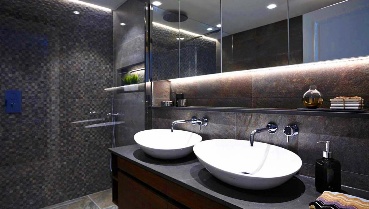 Discovery Dock Bathroom dark bathroom interior with white sinks and polished chrome taps with mirrored panel above with lighting underneath that lights the sinks.