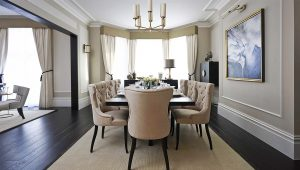 Marlborough Mansions Dining Room in neutral tones with large bay window at the back and a central dark wood dining table surrounded by eight upholstered comfortable chairs with buttons on the back.