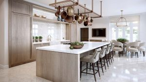 Surrey Home Kitchen, pale wood kitchen units with white work surfaces and copper pans hanging above a central island that has high bar stools on one side to serve as a breakfast bar.