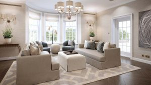 Surrey Home Living Room, neutral interior design colour scheme with a large bay window, neutral and pastel coloured sofas, chairs and pouffe in neutrals, pastel blue and pastel pink, with matching scatter cushions.