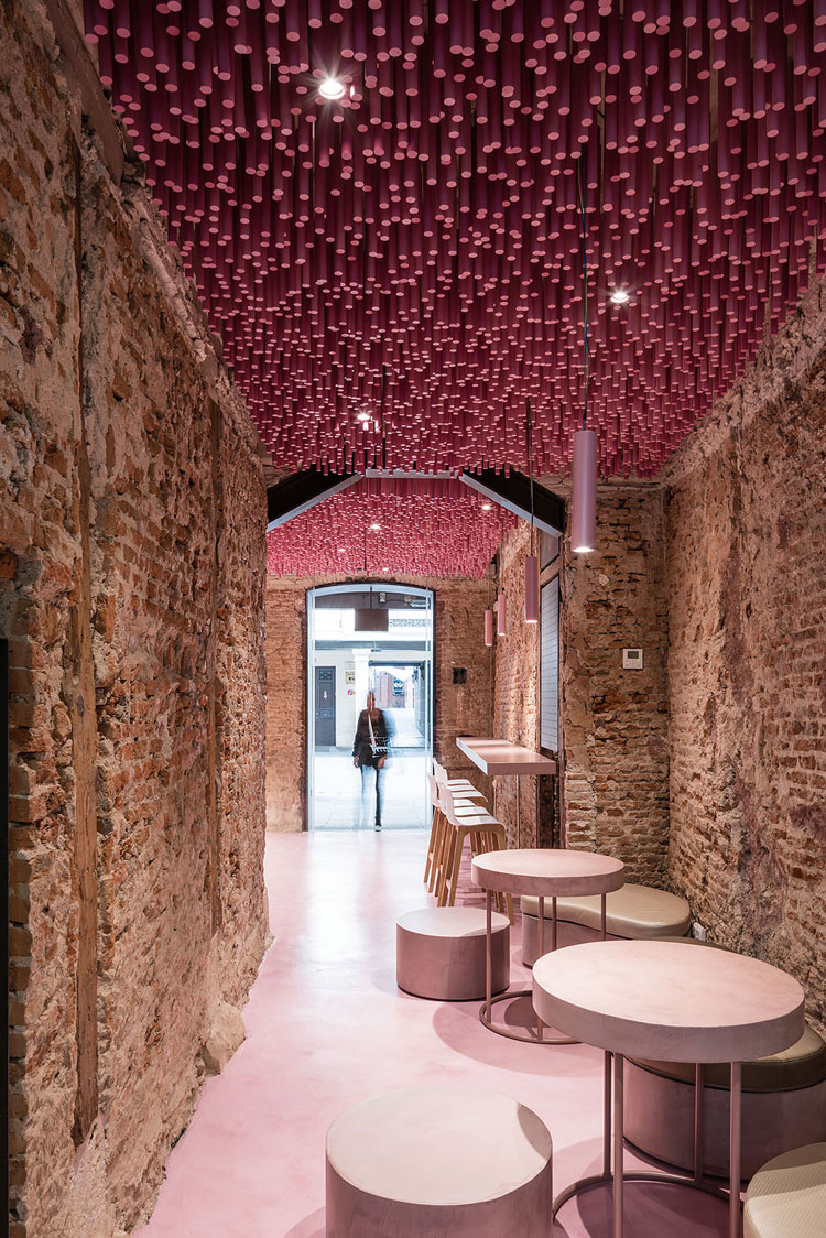 Historic brick bakery interior with modern installation of 12,000 magenta pink wooden rods hanging from the ceiling.
