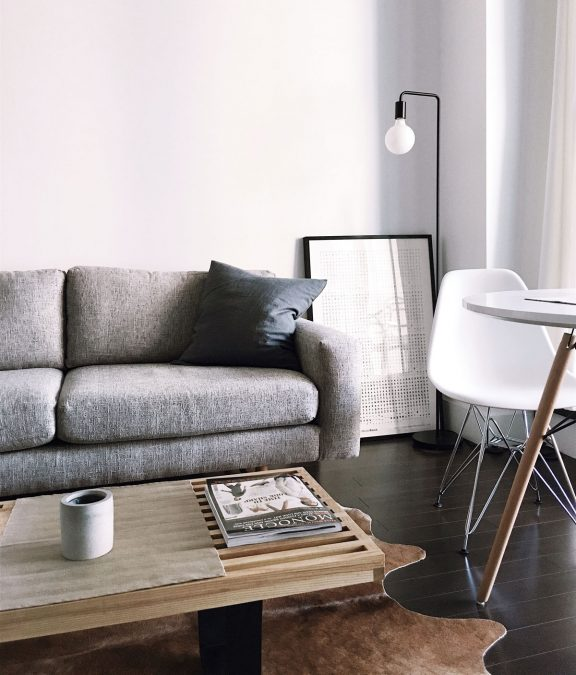 Modern-Interior-Design with white walls and grey sofa, wooden coffee table with magazine