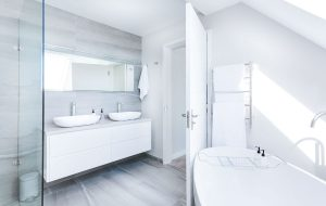 Light and airy white bathroom interior with a light grey tiled feature wall behind the sinks and shower