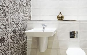 Bathroom interior design with a patterned tile feature wall on one side