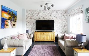 Living room interior in purple tones with floral purple wallpaper and matching roman blind fabric, grey sofas, purple rug and colourful beach artwork
