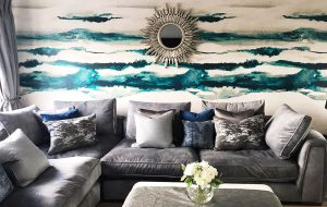 Blue and grey living room interior with large grey sofa, blue and teal abstract wallpaper and round mirror