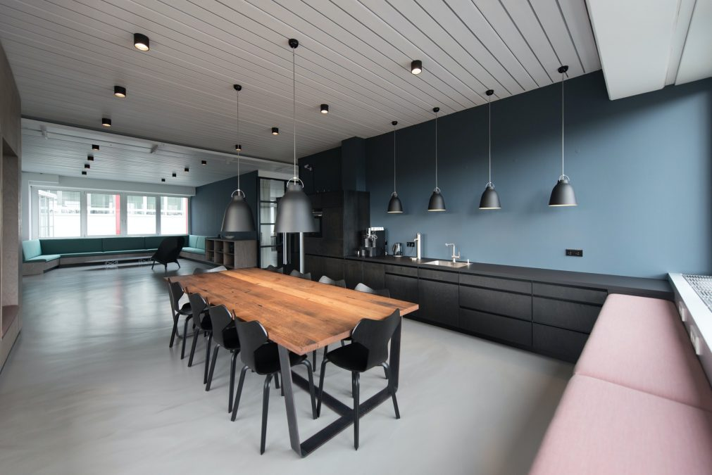 Commercial Workspace Interior with blue walls, black modern kitchen, oak wood dining table and modern industrial interior